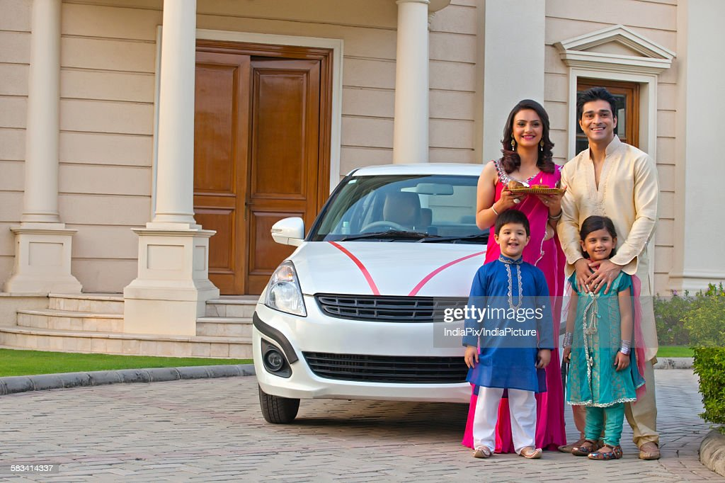 Family standing next to new car : Stock Photo