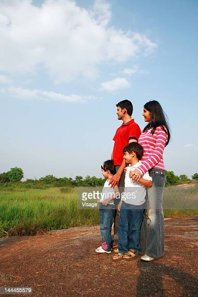 Family standing on a rock