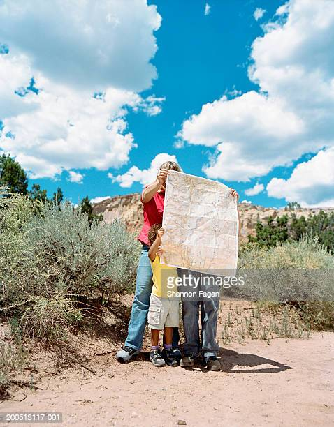 Family standing on desert track looking at map, obscuring faces