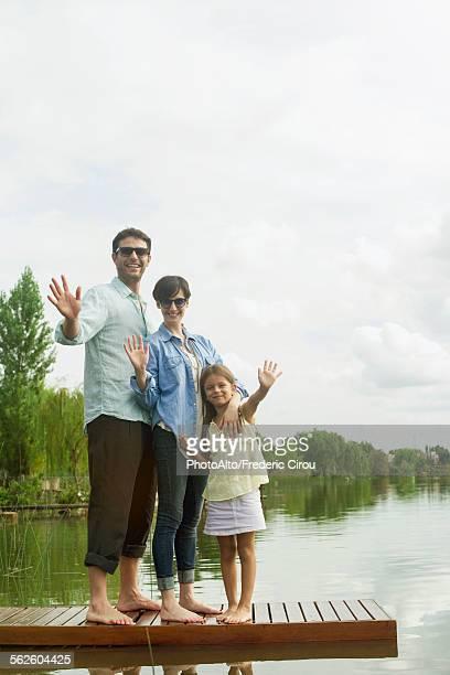 Family standing on dock waving