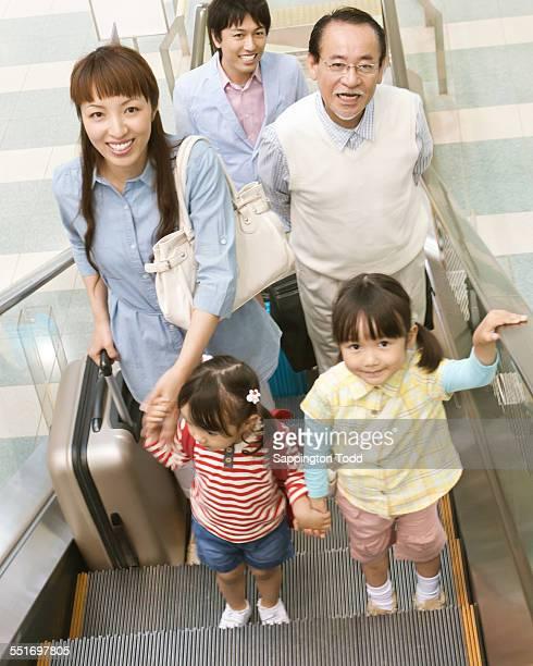 Family Standing On Escalator