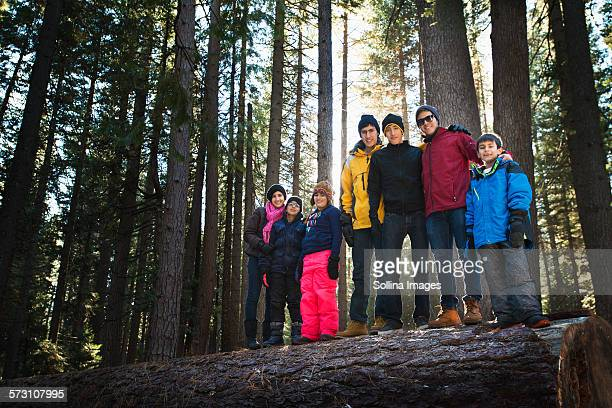 Family standing on log in remote forest