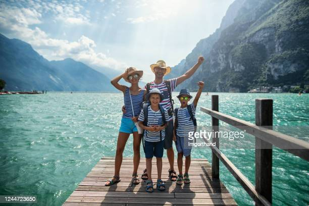 family standing on pier and enjoying view of lake garda - férias imagens e fotografias de stock