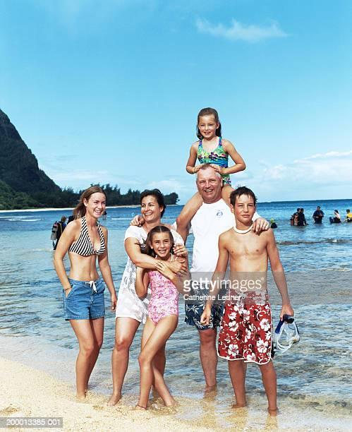 Family standing on shore of ocean, portrait