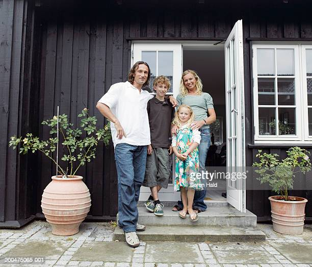 Family standing on steps of house, smiling, portrait