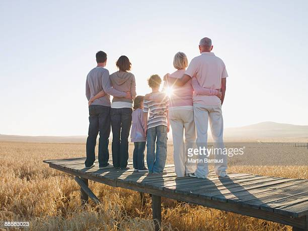 Family standing on wooden dock in remote wheat field