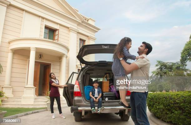 Family standing outdoors by car father lifting daughter