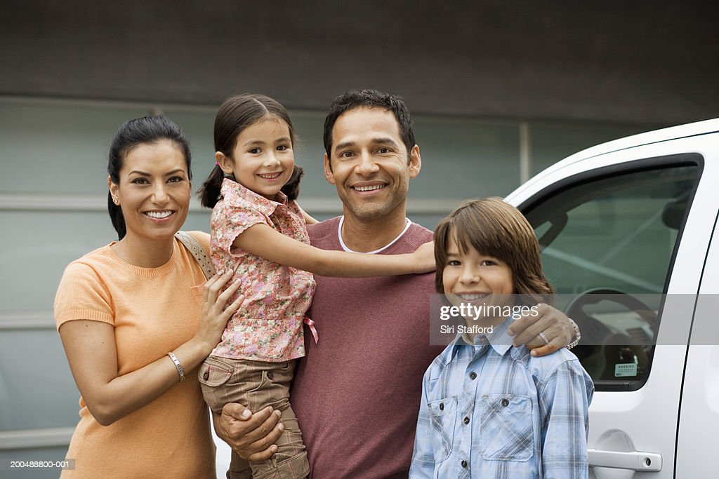 Family standing outside house next to car : Stock-Foto