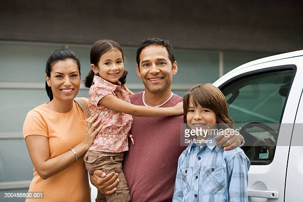 family standing outside house next to car - vier personen stockfoto's en -beelden