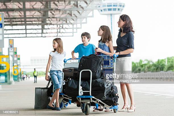Family standing outside of airport with luggage