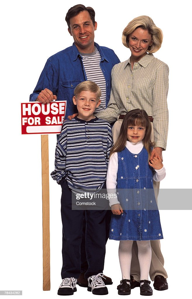 Family standing with a house for sale sign : Stockfoto