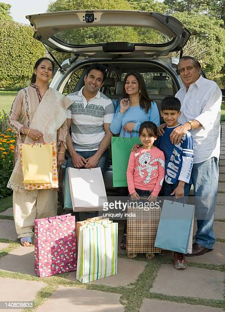 Family standing with shopping bags in front of a car