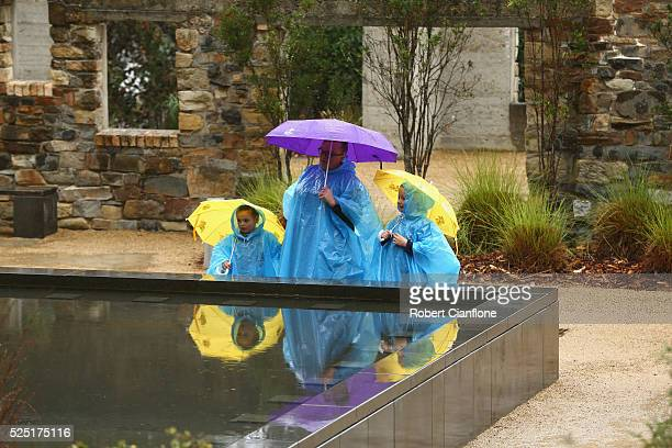 Family stands at the memorial pool, with the Broad Arrow cafe behind them during the 20th anniversary commemoration service of the Port Arthur...