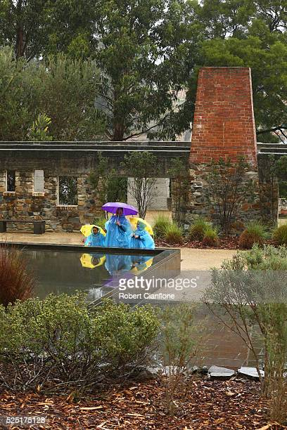 A family stands at the memorial pool with the Broad Arrow cafe behind them during the 20th anniversary commemoration service of the Port Arthur...