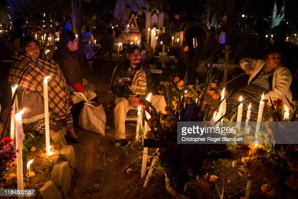 A family stands guard around the grave of their dead relatives in the cemetery of Atzompa Oaxaca as part of the celebrations of the 'Day of the Dead'...