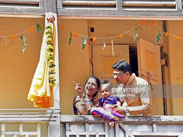 Family stands near a gudi during Gudi Padwa celebrations at Girgaum on April 8, 2016 in Mumbai, India. Gudi Padwa is the Sanskrit name for Chaitra...