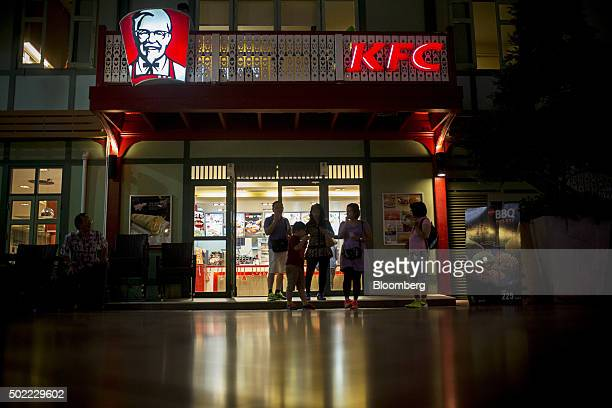 A family stands outside a Yum Brands Inc KFC restaurant at Asiatique The Riverfront openair mall in Bangkok Thailand on Friday Dec 18 2015 Thai...