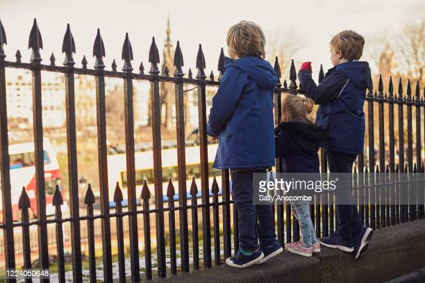 family stood on a fence looking out at the view of the city - edinburgh scotland stock pictures, royalty-free photos & images