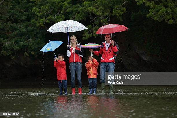 family stood on flooded road in the rain