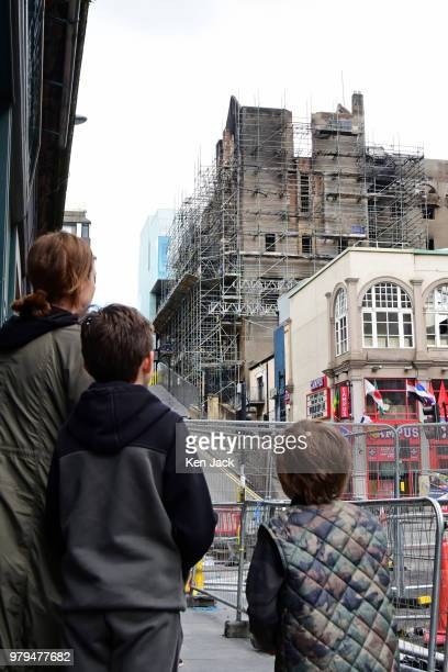 A family stops to look at the remains of the Glasgow School of Art Mackintosh building which was completly burned out in a major fire still carry...