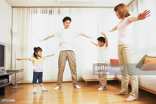 A family stretching in living room