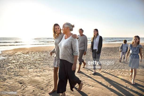 family strolling on the beach at sunset - schleswig holstein stock pictures, royalty-free photos & images