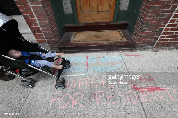 A family strolls along Oak Street in the Chinatown neighborhood of Boston on Oct 5 where protestors have marked the sidewalk in front of an Airbnb...