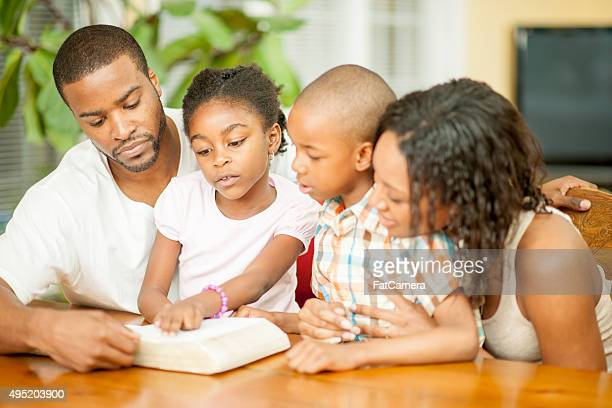family studying the bible together at home - the god father stock photos and pictures