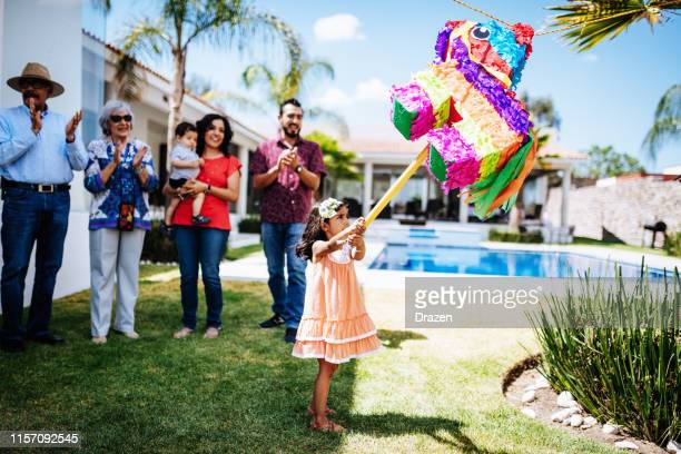 family supports young latina girl when punching piñata - pinata stock pictures, royalty-free photos & images