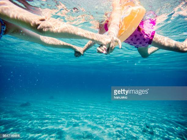 Family swimming and holding hands in the sea