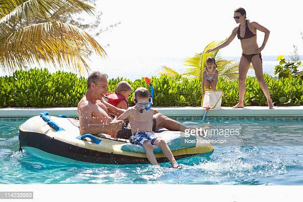 family swimming in pool at a tropical destination
