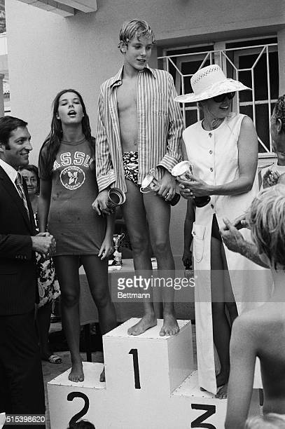 Family Swimming Relay Winners Monaco Princess Grace holds her daughter Stephanie's cup as she poses on the podium at the Monte Carlo Beach with her...