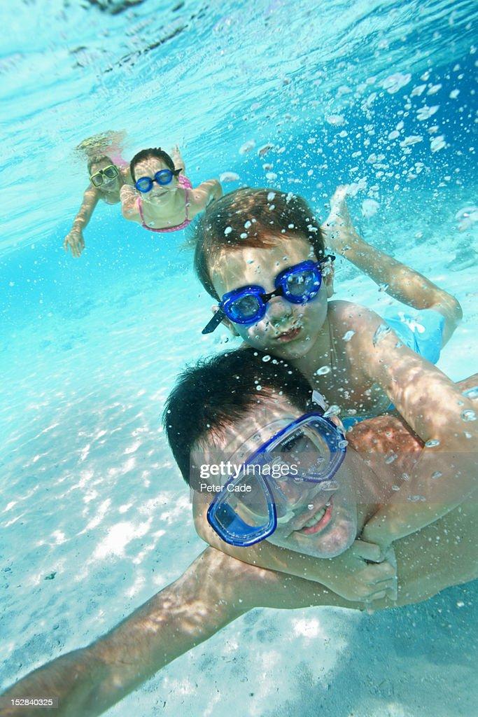 Family swimming underwater in sea : Stock Photo