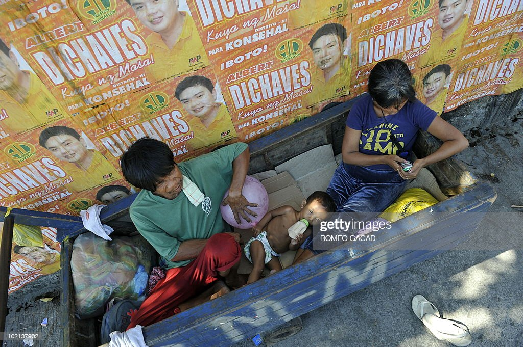 A family take a rest on their cart next to election posters along a side street in Manila on May 6, 2010. Philippines election officials insisted that next week's polls would go ahead, amid frantic efforts to replace more than 70,000 faulty memory cards that were to be used in vote counting machines.