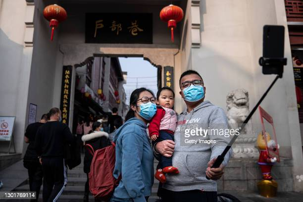 Family take a selfie on a popular street for restaurants during the first day of the Spring Festival on February 12, 2021 in Wuhan, Hubei Province,...