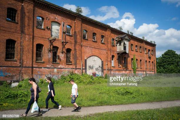 A family take a short cut from the shops past the derelict Great Northern Railway Bonded Warehouse on May 31 2017 in Derby England The Derby North...