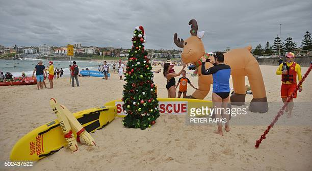 A family take photos of a Christmas tree and an inflatable reindeer on Bondi Beach in Sydney on December 25 2015 Sydney's iconic Bondi Beach is a...