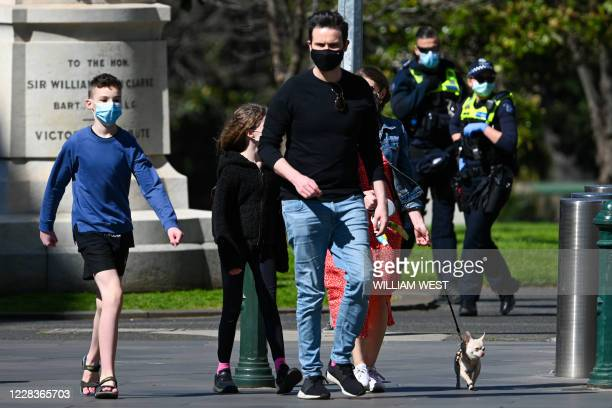 Family takes a walk as police look on in Melbourne on September 6, 2020 as the state announced an extension to its strict lockdown law while it...