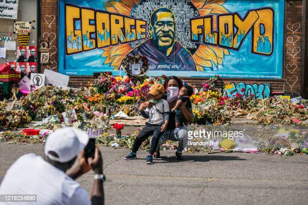 A family takes pictures in front of a mural of George Floyd on June 10 2020 in Minneapolis Minnesota People have been gathering at the memorial site...