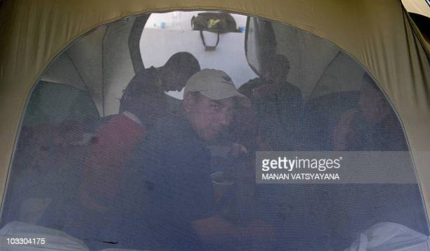 A family takes shelter inside a tent at the Buddhist Shanti Stupa in Leh on August 9 2010The death toll from flash floods in India's remote Himalayan...