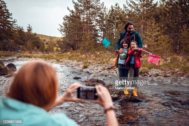 family taking a picture with a fish they caught - photo messaging stock pictures, royalty-free photos & images