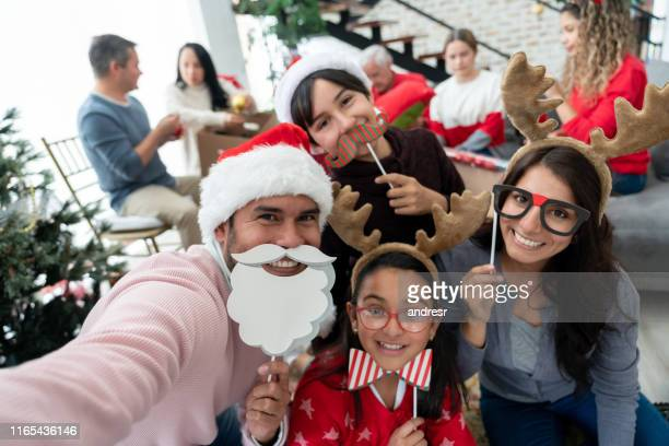 family taking a selfie on christmas day using props - christmas photos stock photos and pictures