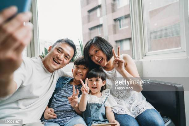 family taking a selfie sitting on the sofa at home - taiwan stock photos and pictures