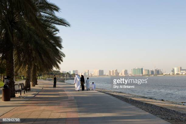 a family taking a walk by the bay. - boulevard stock pictures, royalty-free photos & images