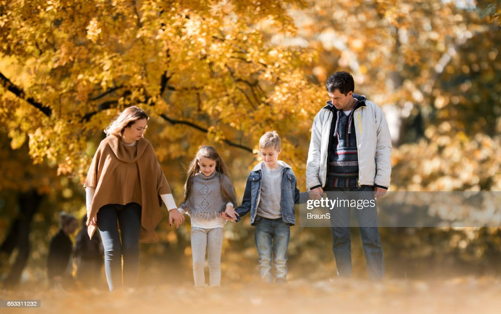 Family taking a walk in autumn day at the park. : Stock Photo