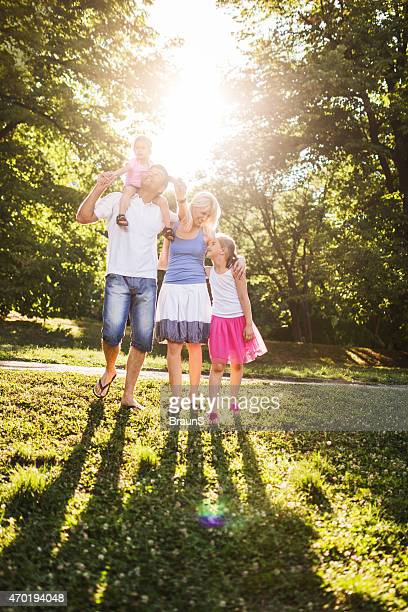 Family taking a walk in the park during sunny day.