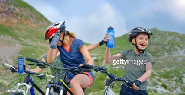 family taking break during mountain biking - fingerless gloves stock pictures, royalty-free photos & images