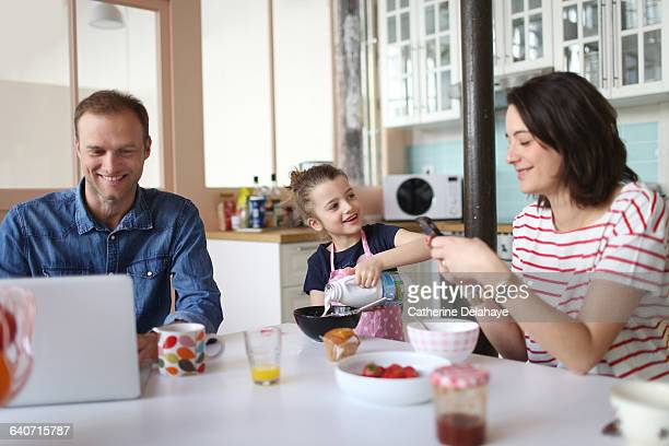 A family taking breakfast in the kitchen