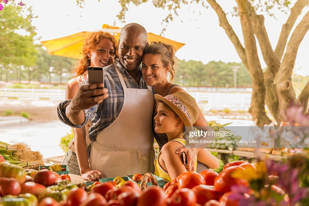 Family taking cell phone selfie at farmers market : Foto stock