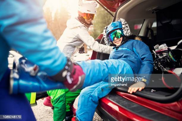 family taking off ski boots after skiing - ski holiday stock pictures, royalty-free photos & images